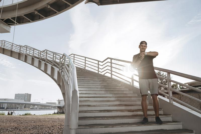 A young athlete stands on the stairs and looks at his smart watch. After a nice jogging royalty free stock photography