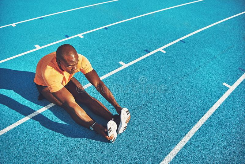 Young athlete stretching on a running track before training stock image