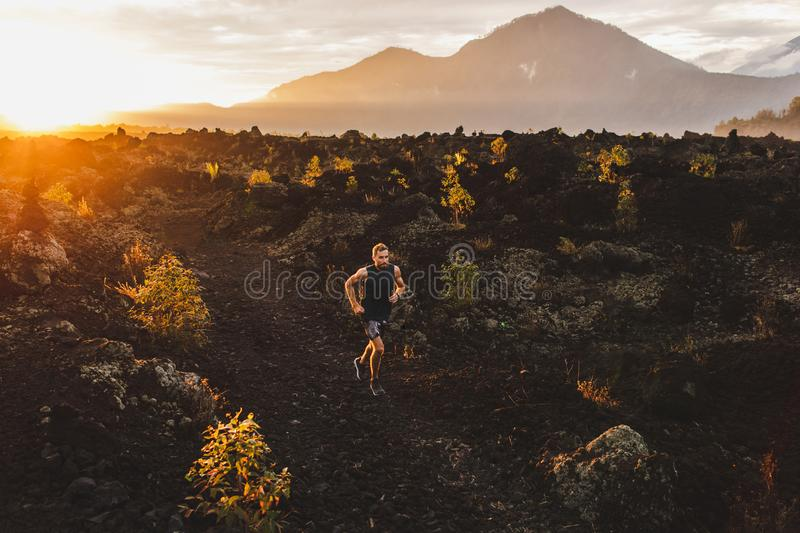Young athlete trailrunning in mountains at sunrise. Young male athlete trail running in mountains at sunrise. Amazing black lava volcanic landscape of Bali on stock images