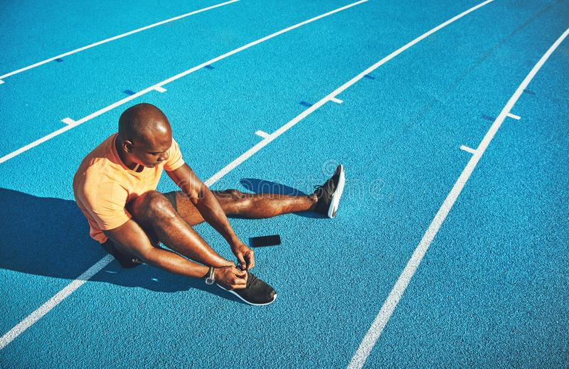 Young athlete tying his shoes before for a track run. Focused young African male athlete sitting alone on a running track tying up his shoes before training royalty free stock photo