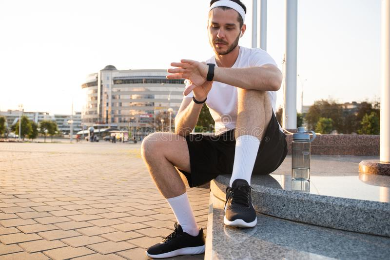 Young athlete in windrunner sitting on the street after good jogging session at sunset. stock images