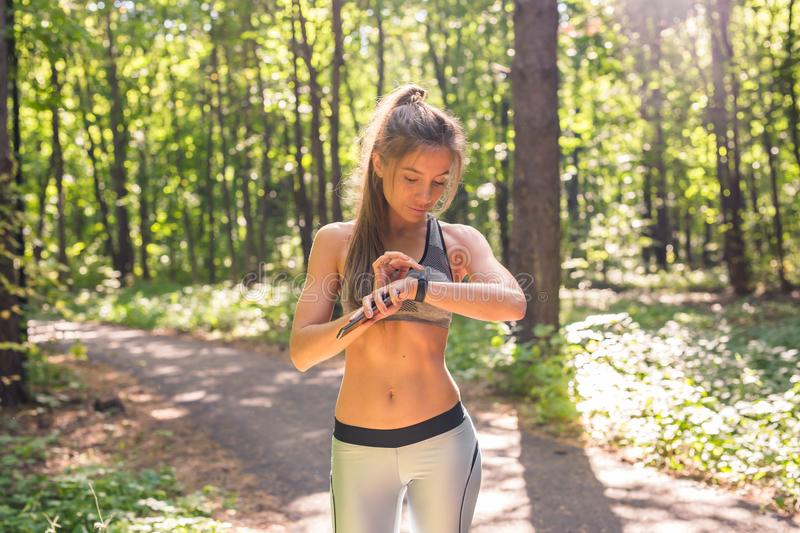 Young athlete woman checking fitness progress on her smart watch. Female runner using fitness app to monitor workout. Performance stock images