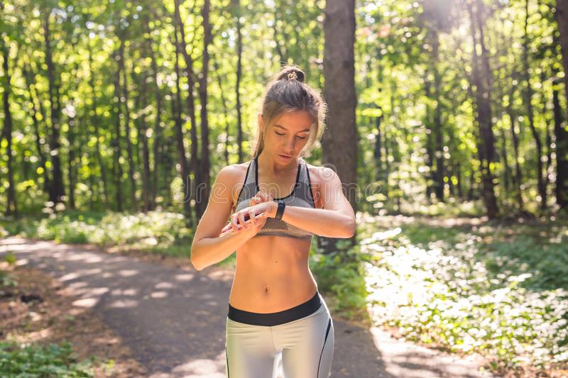 Young athlete woman checking fitness progress on her smart watch. Female runner using fitness app to monitor workout. Performance royalty free stock photos