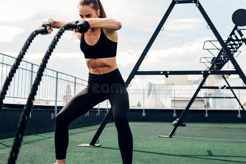 Young athlete working out with two battle ropes royalty free stock photography