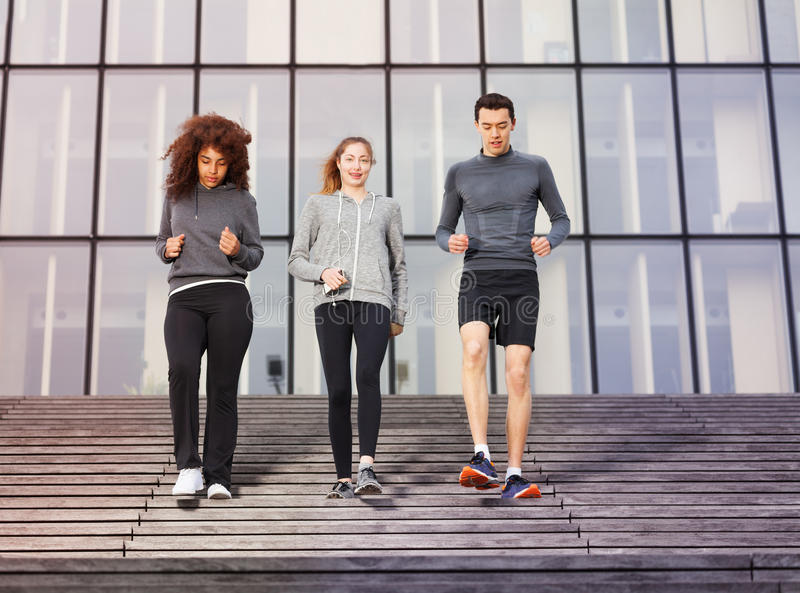 Young athletes going down outdoors on city stairs. Two young women and one men going downstairs as part of their workout outdoors on city stairs stock image