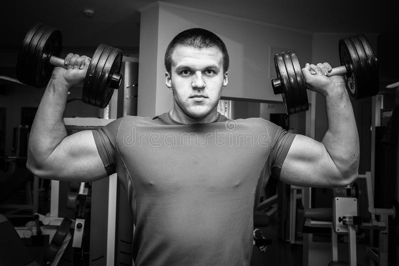 Young athletes in the gym. Work on your body. Performing complex and grueling exercise. Photos for magazines, posters and Web sites stock images