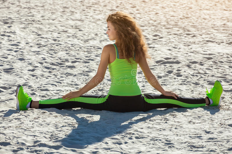 Young athletes - gymnast with curly hair, light green suit and sneakers doing the splits on the beach in summer, morning exercise. stock images