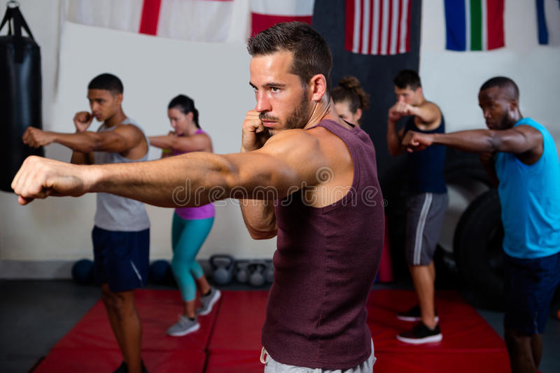 Young athletes practicing boxing against flags royalty free stock image