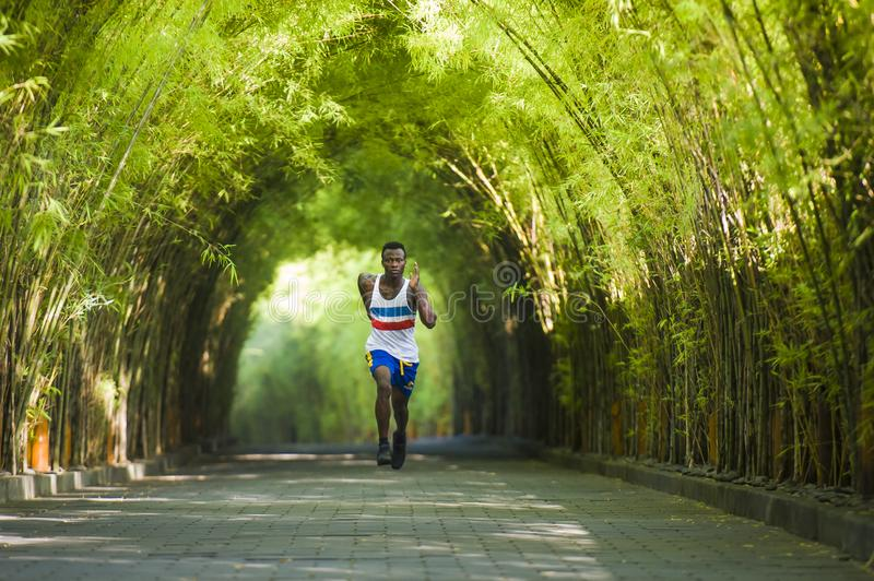 Young athletic and attractive black African American runner man doing running workout training outdoors on urban city park in. Healthy lifestyle portrait of stock photography