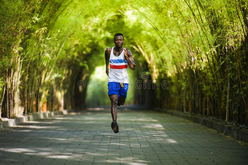 Young athletic and attractive black African American runner man doing running workout training outdoors on urban city park in. Healthy lifestyle portrait of royalty free stock images