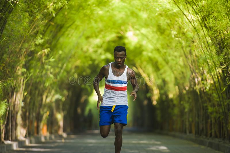 Young athletic and attractive black afro American runner man doing running workout training outdoors on urban city park in fitness. Healthy lifestyle portrait of royalty free stock photography