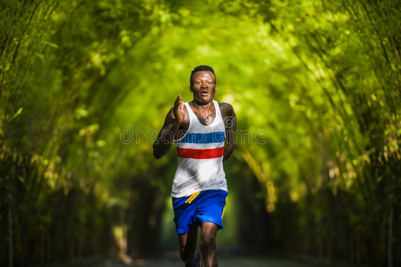 Young athletic and attractive black afro American runner man doing running workout training outdoors on urban city park in fitness stock photos