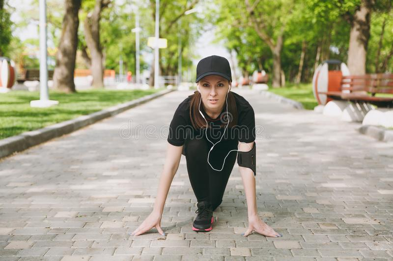 Young athletic beautiful brunette girl in black uniform and cap with headphones listening music at low start before royalty free stock photo