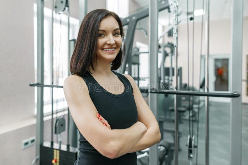 Young athletic confident woman fitness instructor posing in gym with folded crossed arms, looking in camera royalty free stock image