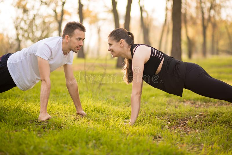 Young athletic couple doing push up outdoors. Athletic family engaged in sports on nature stock photography