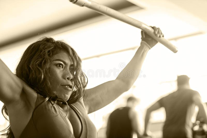 Young athletic and determined Asian Indonesian woman working weights using chest bodybuilding gym machine at fitness club royalty free stock photography