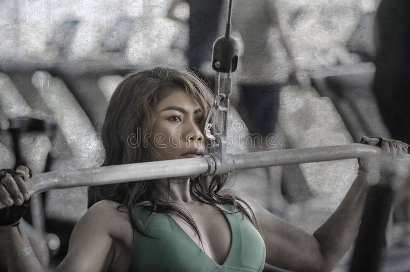 Young athletic and determined Asian Indonesian woman working weights using chest bodybuilding gym machine at fitness club stock photo