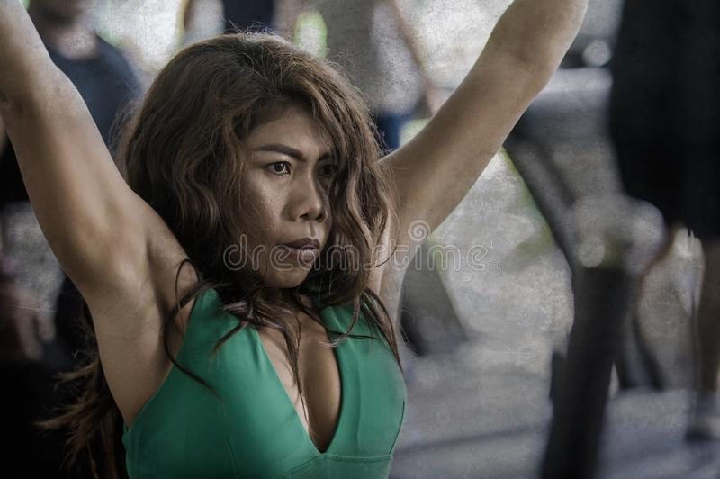 Young athletic and determined Asian Indonesian woman working weights using chest bodybuilding gym machine at fitness club stock photography