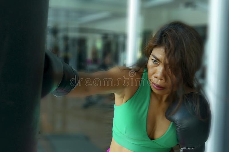 Young athletic and fit attractive Asian fighter woman punching heavy bag with boxing gloves at fight club gym doing hard workout royalty free stock photography