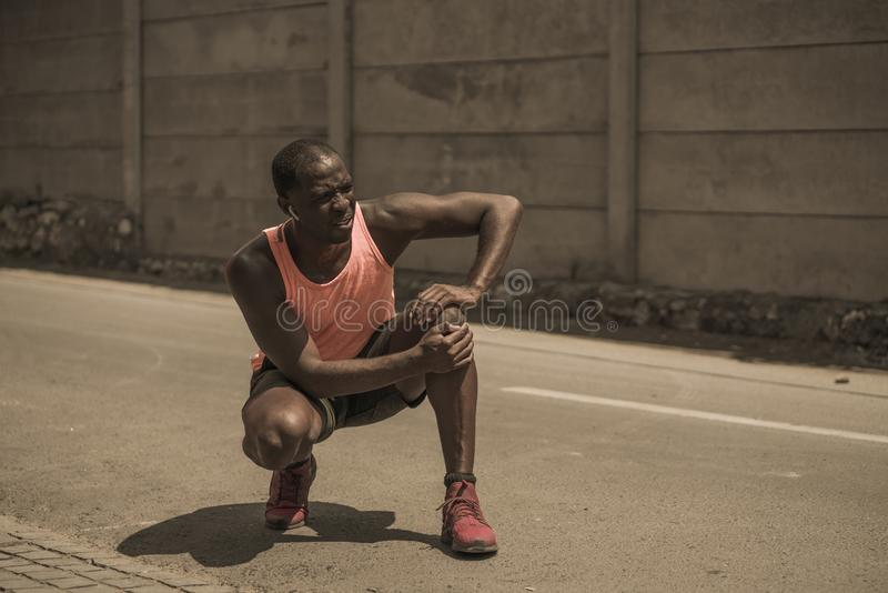 Young athletic and fit black afro American runner in pain holding his knee after suffering medical problem with injuried tendon or stock photo