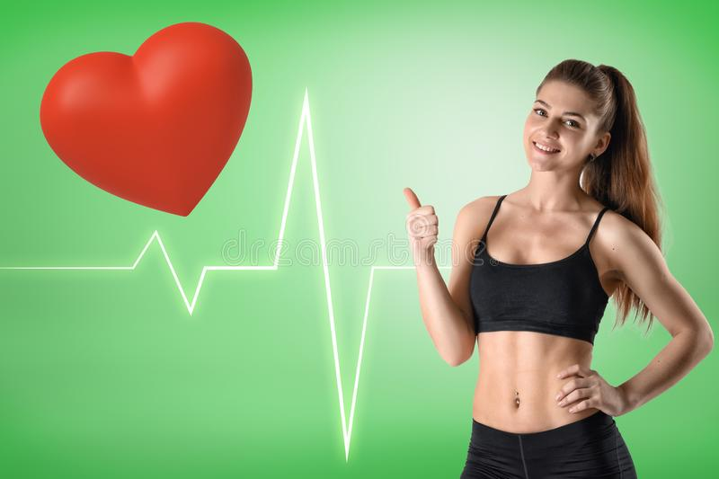 Young athletic fitness girl with red heart and heart rhythm cardiogram on green background royalty free stock photos