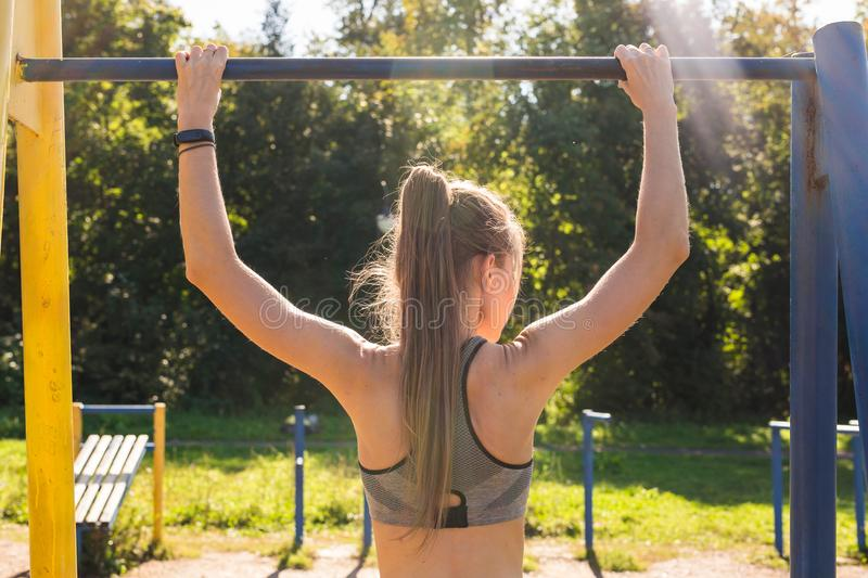 Young athletic fitness woman working out at outdoor gym doing pull ups at sunrise. Young athletic fitness woman working out at outdoor gym doing pull ups at royalty free stock photos