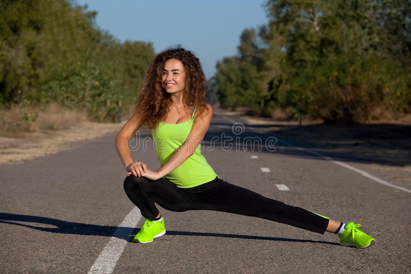 Young athletic girl in black-green tracksuit doing morning sports training in the park. stock photo