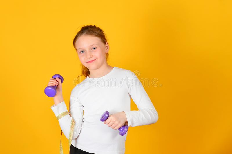 Young and athletic girl does physical exercises with dumbbells, on a yellow background stock photo