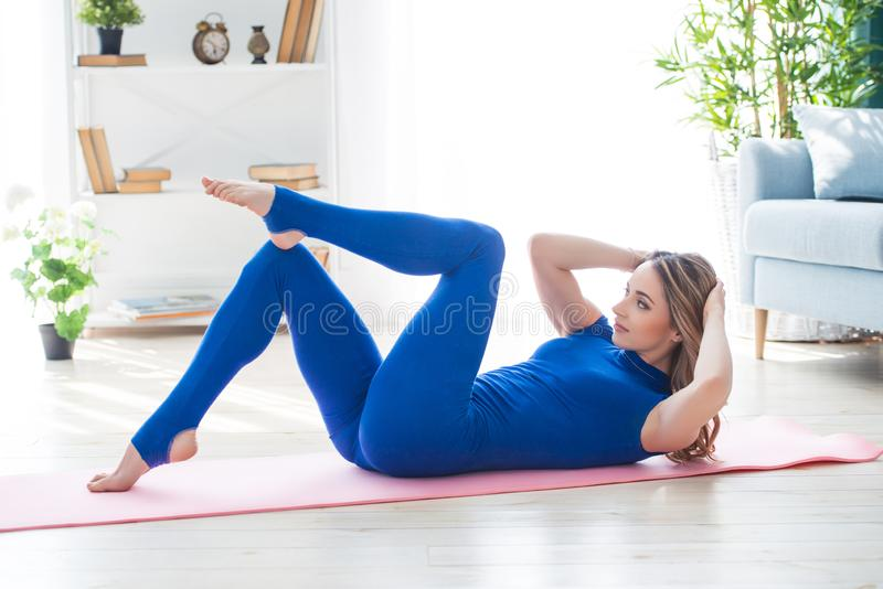 Young athletic girl fitness trainer in blue sports overalls shows morning gymnastic exercises in the interior of the room. Exercise press royalty free stock photo