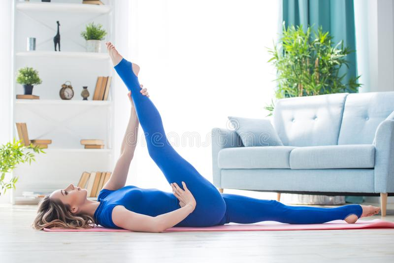 Young athletic girl fitness trainer in blue sports overalls shows morning gymnastic exercises in the interior of the room. Stretching for twine stock images