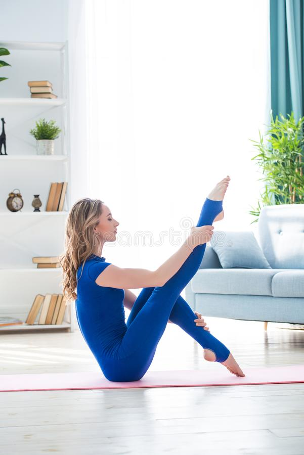 Young athletic girl fitness trainer in blue sports overalls shows morning gymnastic exercises in the interior of room. Stretching. And swinging legs royalty free stock image