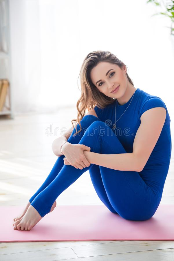 Young athletic girl fitness trainer in blue sports overalls shows morning gymnastic exercises and yoga poses in the interior of. The room stock images