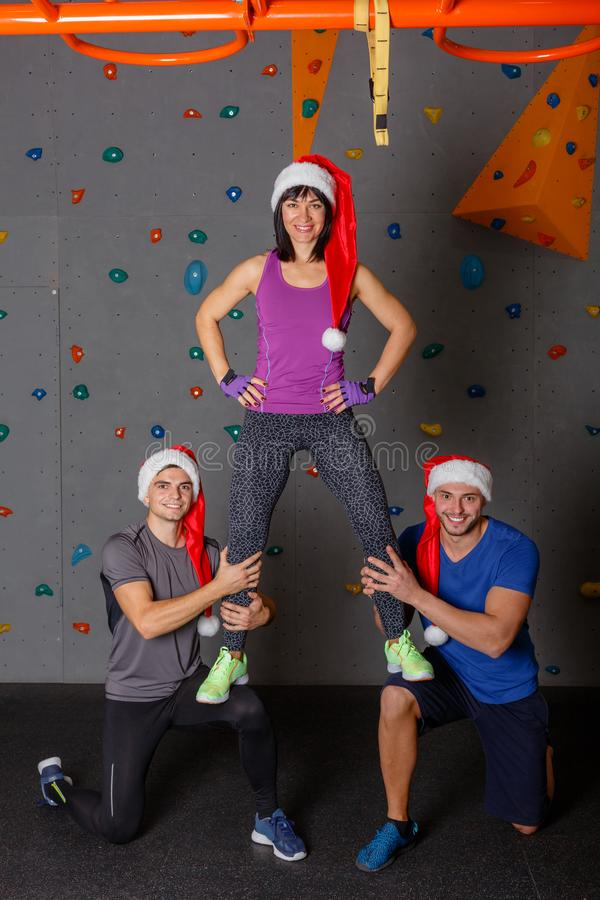 A athletic girl is kneeling beside the athletic guys. They smile and are in Christmas hats. stock image