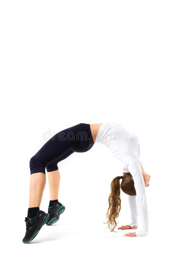 Young athletic girl makes gymnastic bridge, isolated royalty free stock image