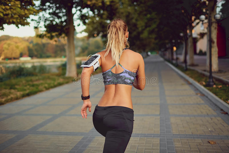 Young athletic girl runner jogging in park in summer autumn. Back view stock photo