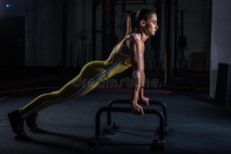 Young athletic girl in yellow tight sports uniform doing horizontal push-ups with bars in gym.  royalty free stock photos