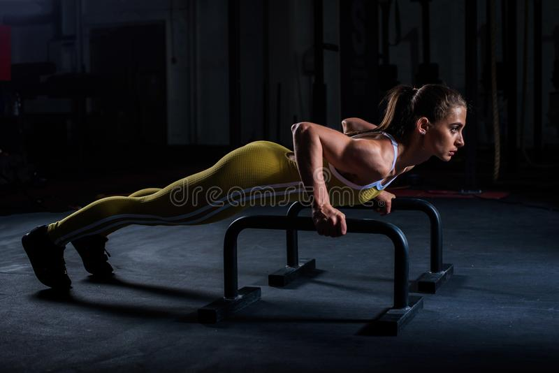 Young athletic girl in yellow tight sports uniform doing horizontal push-ups with bars in gym.  stock photos