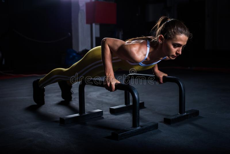 Young athletic girl in yellow tight sports uniform doing horizontal push-ups with bars in gym.  royalty free stock image