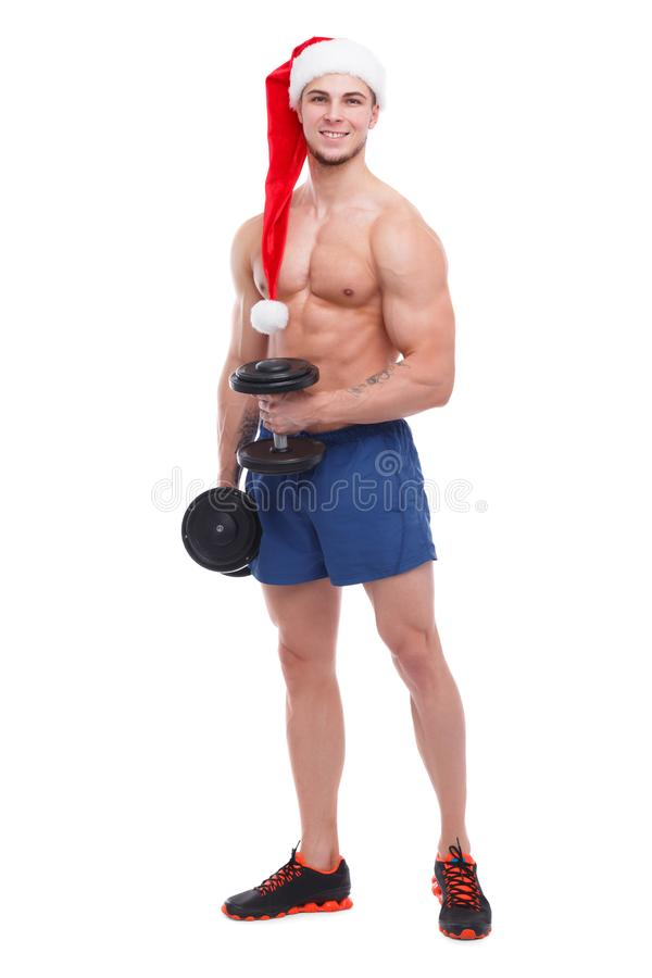 A athletic guy with a naked torso and a santa hat is standing with a dumbbell in his hands. A young athletic guy with a naked torso and a santa hat is standing stock photography