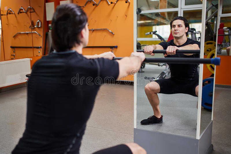 Young athletic man in black sportwear with bar of barbell flexing muscles in gym in front of the mirror. stock photography