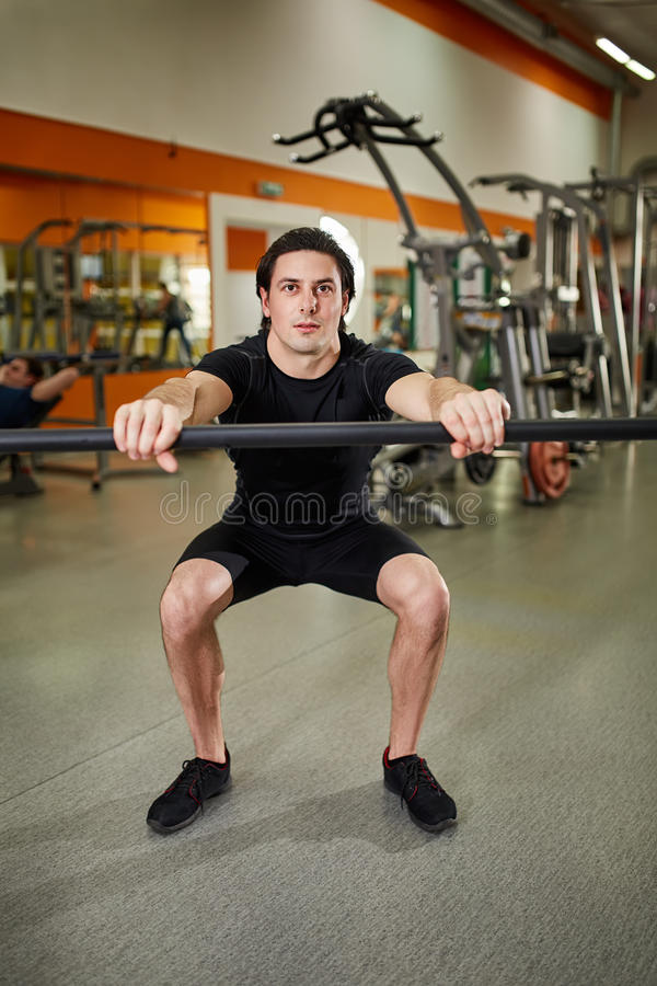 Young athletic man in black sportwear with bar of barbell flexing muscles in gym. royalty free stock photo