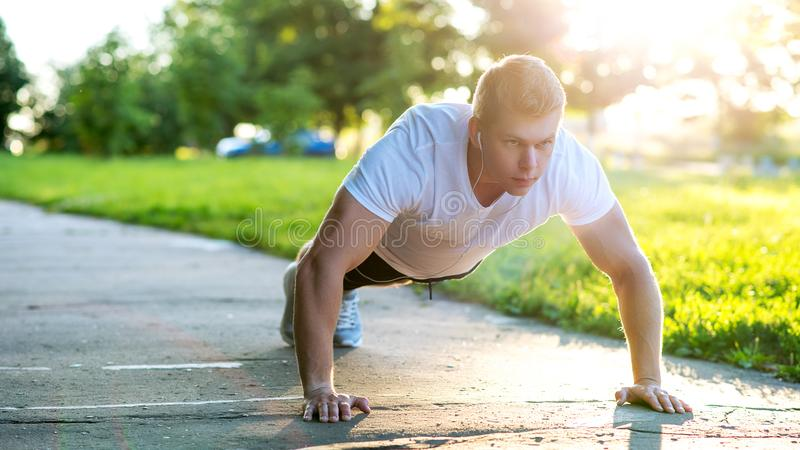 A young athletic man does push-ups. A muscular and strong guy is training. In nature in the park in the summer. Strength. A young athletic man does push-ups. A royalty free stock photo