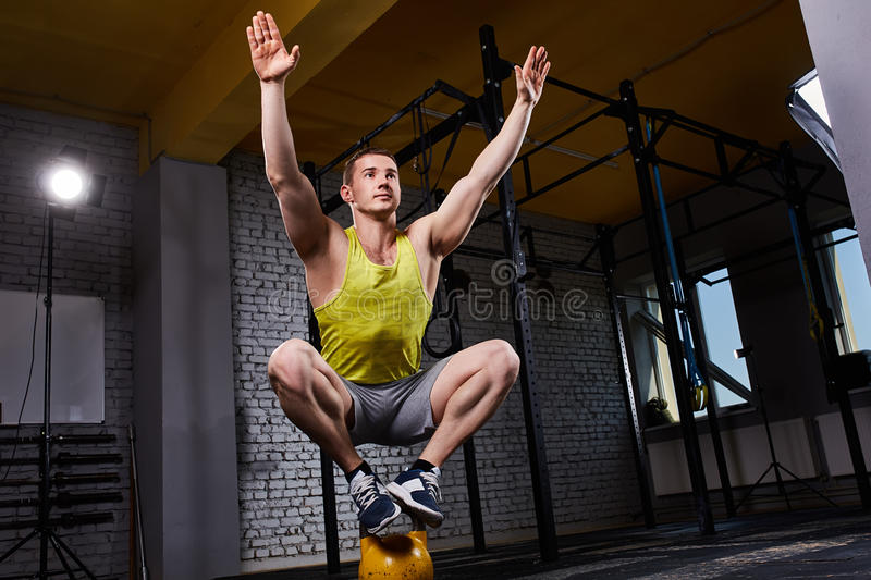 Young athletic man doing exercises in cross fit gym while crouching on two legs on the kettlebell. stock photo