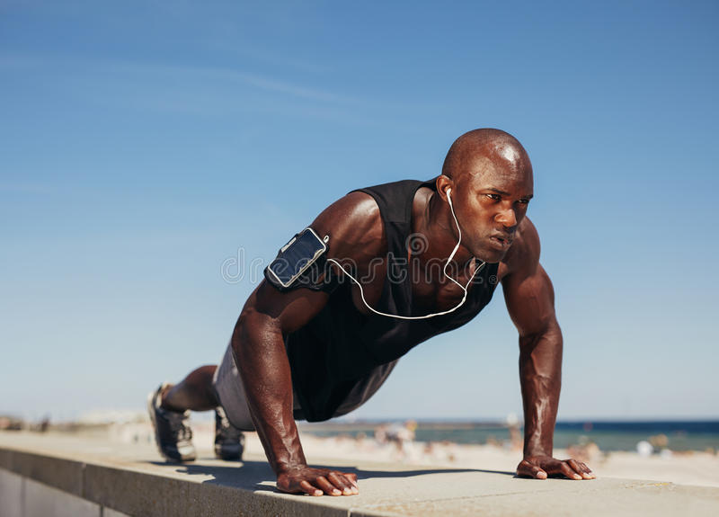 Young athletic man doing push-ups. Fitness model doing outdoor workout. Muscular and strong guy exercising royalty free stock images