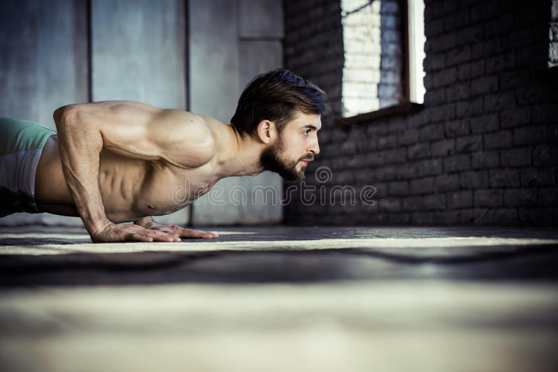 Young athletic man doing push-ups. royalty free stock image