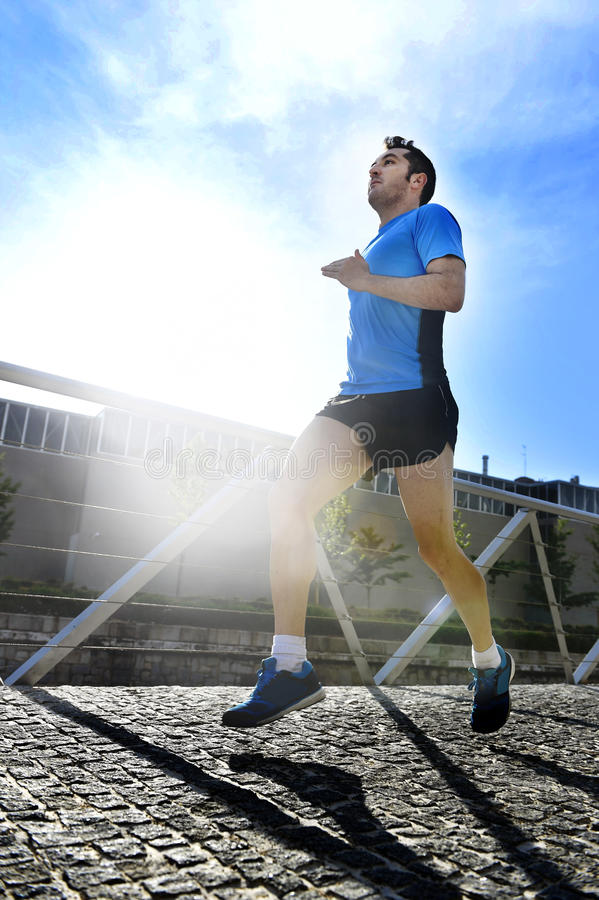 Young athletic man practicing running in urban background backlight in fitness sport training and healthy lifestyle concept royalty free stock photo