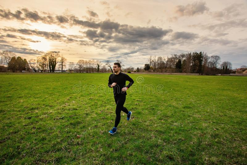 Workout jogging activity. Young athletic man practicing sport outdoors city park. Self overcome conquering obstacles and win. Healthy lifestyle concept. Workout stock photo
