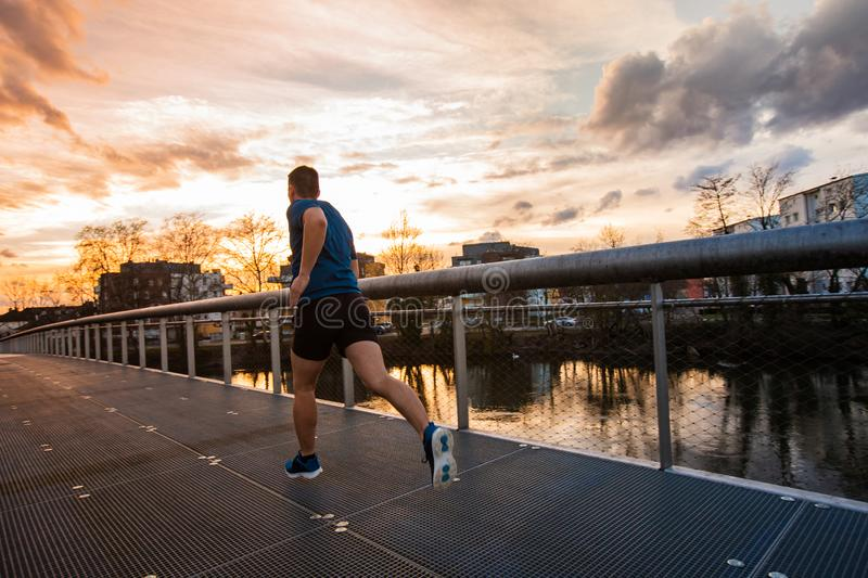 Healthy lifestyle concept. Young athletic man practicing sport outdoors, running fast along bridge over the sunset sky background. Self overcome conquering royalty free stock image