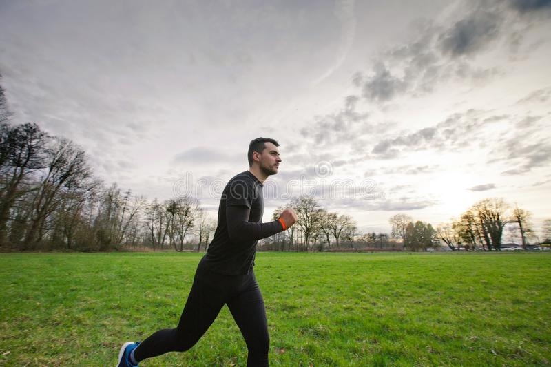 Young athletic man practicing sport outdoors. City park. Self overcome conquering obstacles and win. Healthy lifestyle concept. Workout jogging activity royalty free stock image
