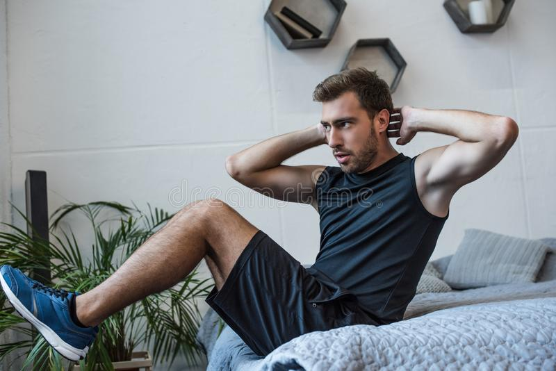 Young athletic man in sportswear doing exercises for abs royalty free stock image